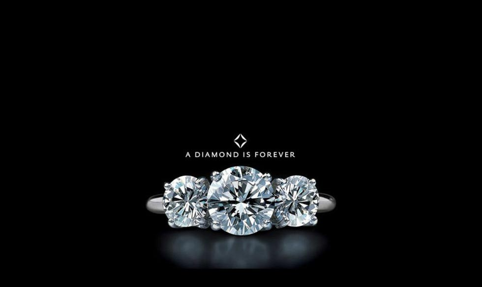 """De Beers' advertising slogan """"A Diamond Is Forever"""" featuring a trio of diamond engagement rings"""