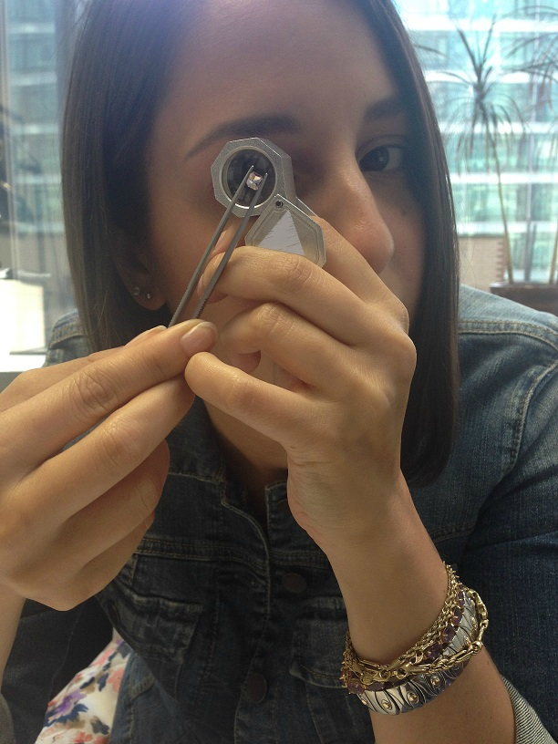 Jeweler inspecting loose pink diamond under loupe