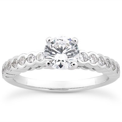 Contemporary style engagement ring with bezel set pave diamond band
